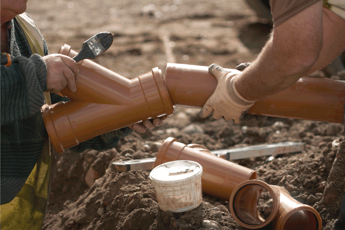 Two Builders holding PVC pipework whilst preparing it for joining prior to fitting it in the ground. What Is The Best Pipe To Use For Drainage