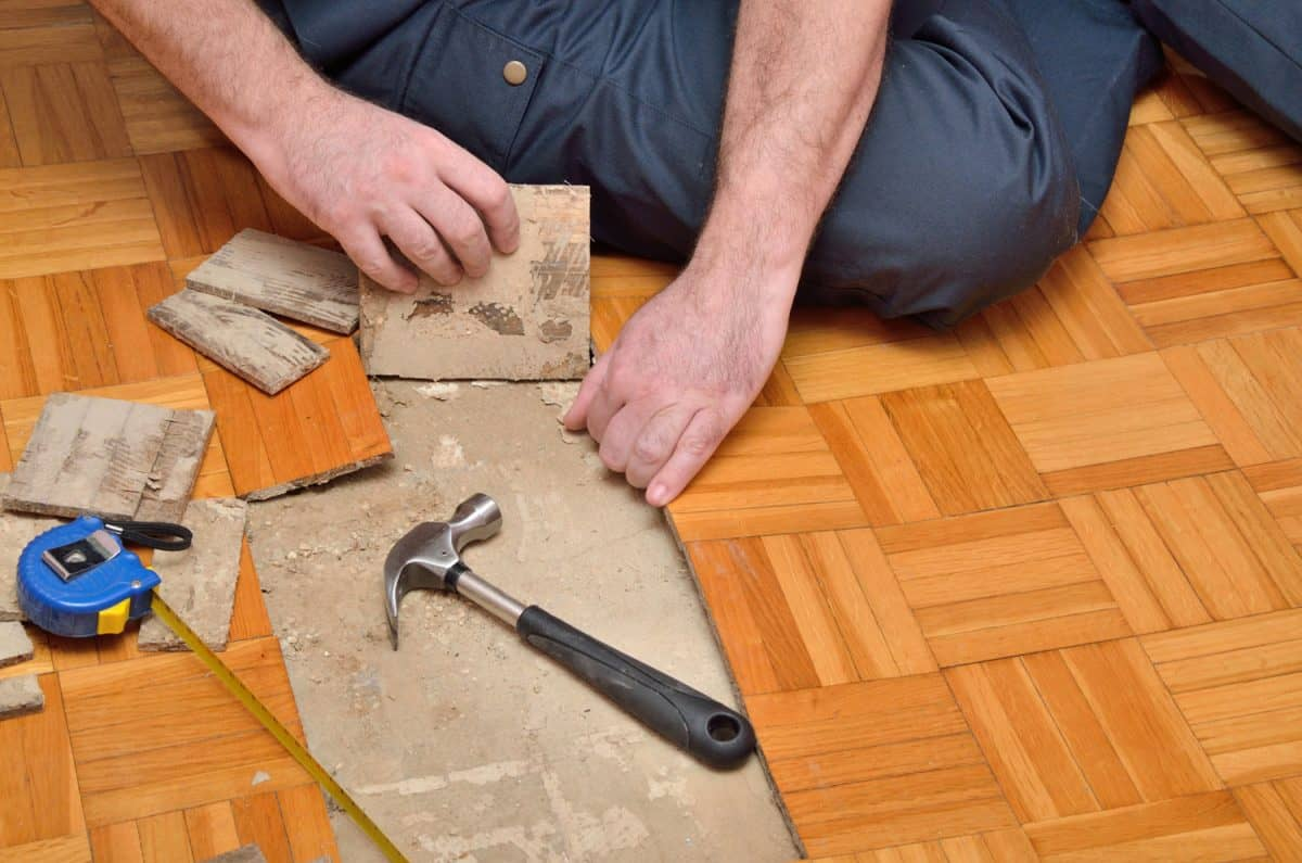 Worker removing pieces of parquet damaged by moisture or water