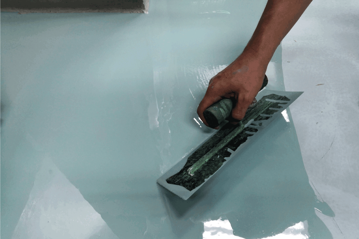 Construction worker painting the floor using self-leveling epoxy spreading with trowel. Best Epoxy Coating Products For Concrete Floors [7 Fantastic Choices]